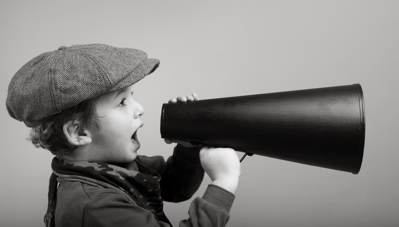 Junge mit Kappe und einem alten Megafon.