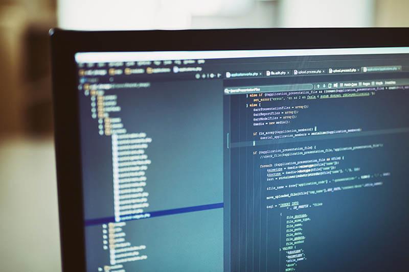 ภาพรหัสเว็บไซต์ด้านหลังบนหน้าจอคอมพิวเตอร์ นักพัฒนาซอฟต์แวร์ทำงานในโครงการเว็บในสำนักงานที่วุ่นวาย ในภาพมีความลึกตื้น มีบรรทัดรหัสในไฟล์