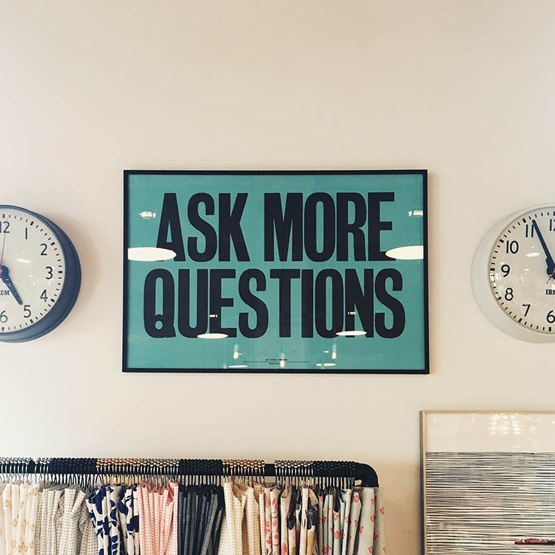 "A sign reading ""ASK MORE QUESTIONS"" in all-caps on a wall between two analog clocks."