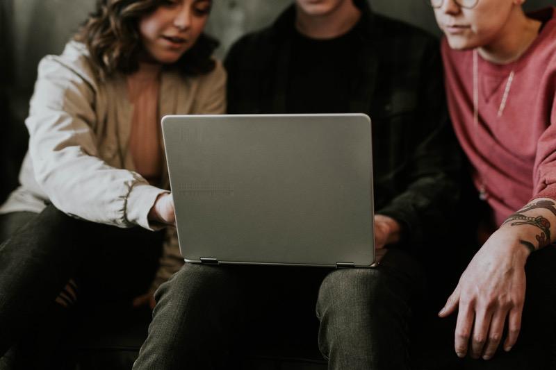 คนสามคนนั่งอยู่รอบ ๆ คอมพิวเตอร์ที่ทำงานร่วมกัน