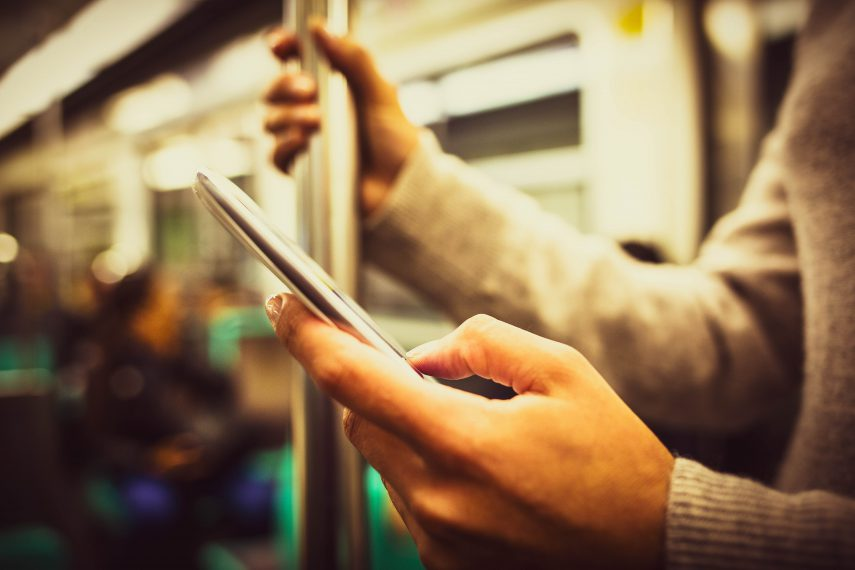 hand holding phone on a subway