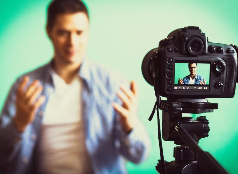 man sitting in front of video camera