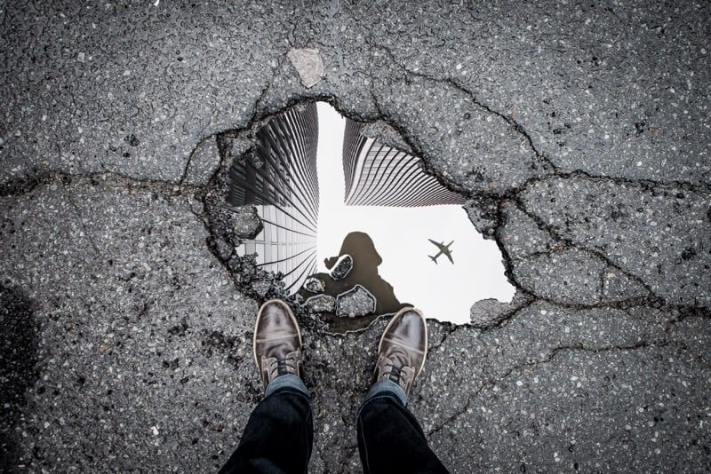 a man stands on asphalt near puddle taking picture