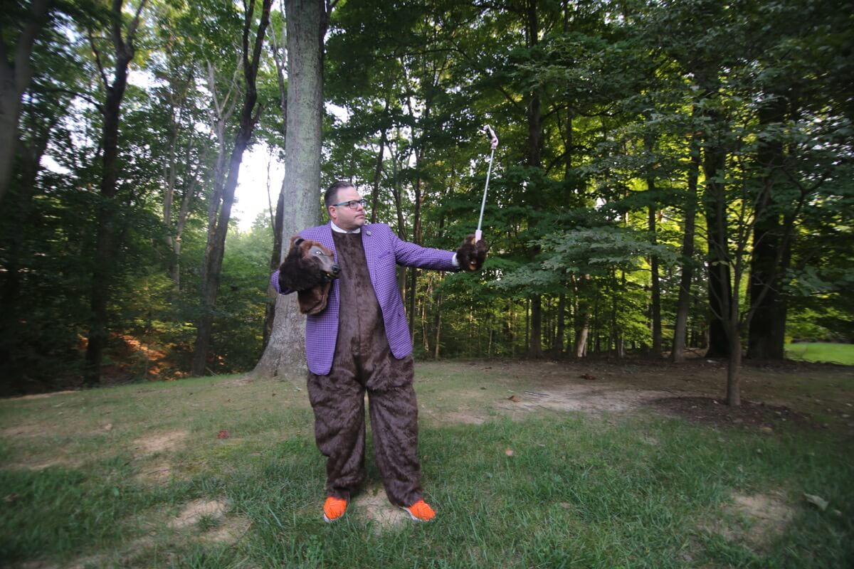 Jay Baer in a bear suit standing on grass with a forest in the background.