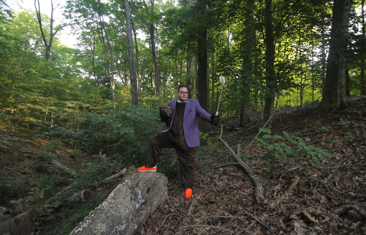 Jay Baer wearing his bear suit standing in a thick forest with his foot up on a log and a selfie stick taking his picture