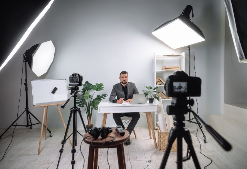 man sitting at desk with video lighting and camera set up