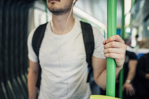 Student on a jostling bus, using headphones to listen to a video lesson with audio descriptions