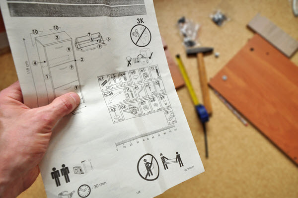 Person holding an instruction page while trying to assemble something.