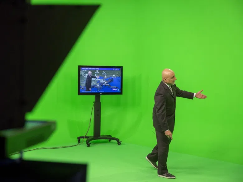 A weather presenter standing in front of a green screen. A TV monitor shows how he looks superimposed over the weather map.